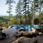 outdoors pool and hot tub in the middle of the woods