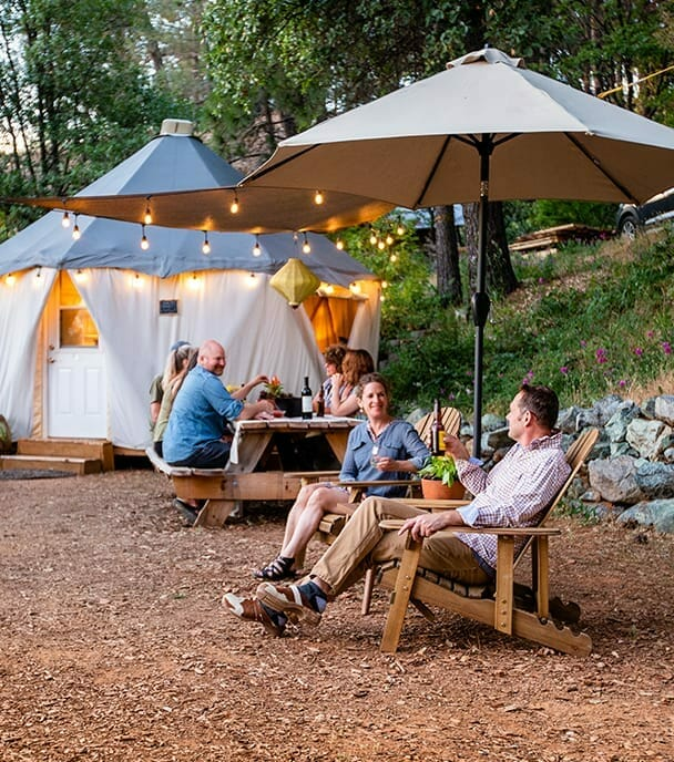 a group of people gathered outside in the garden of the yurt