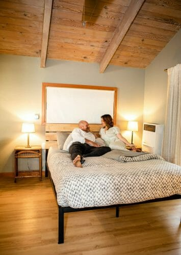 a couple laying on the bed of the reverie retreat cottage