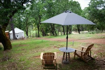 the green view outside blackberry yurt with two outdoor chairs under and umbrella with a picnic table
