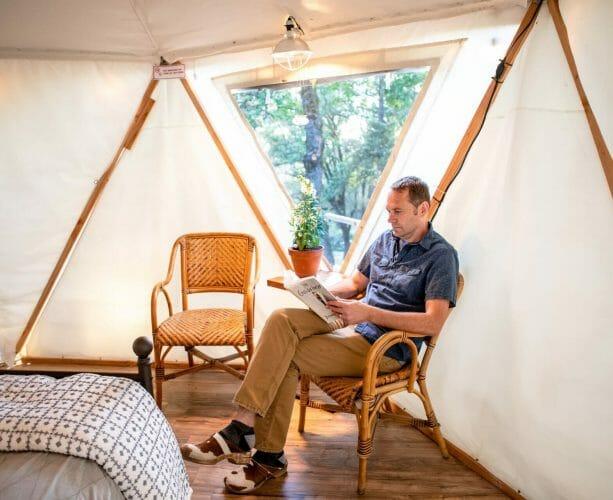 a man sitting inside yurt ponderosa reading a book