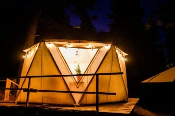 the exteriors of the yurts with lights at night