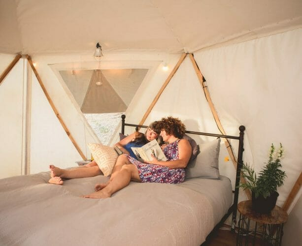 two women laying on the bed at blackberry yurt reading a book