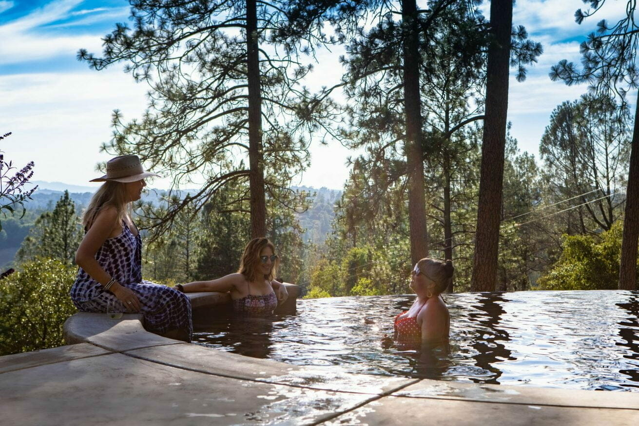 three women talking in the pool in the middle of the woods